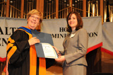 Emily Tamadonfar, Phi Kappa Phi student vice president, accepts the Robert C. Maxson Phi Kappa Phi Graduate Scholarship from Margaret Louis.